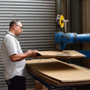 Dakri Cartons employee shaping a carton box.