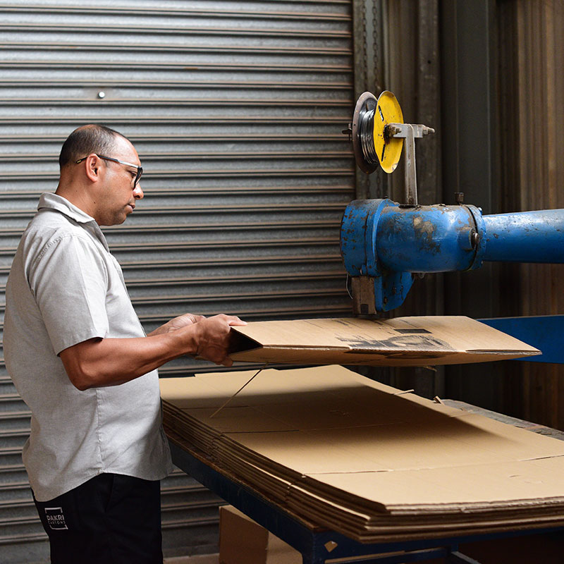 Dakri Cartons employee shaping a carton box.